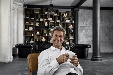 Portrait of mature man enjoying cup of coffee in loft - PDF01604