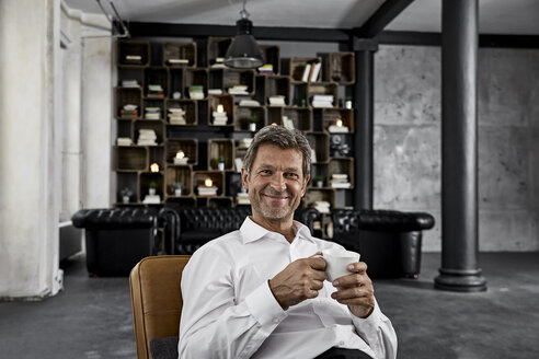 Portrait of mature man enjoying cup of coffee in loft - PDF01604