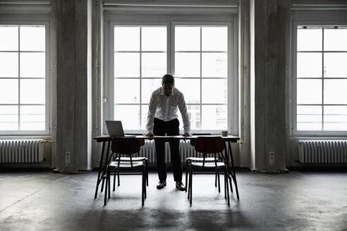 Silhouette of mature businessman in loft - PDF01607