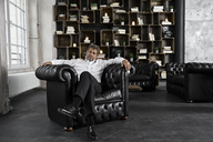 Portrait of mature man sitting in black armchair in loft - PDF01616