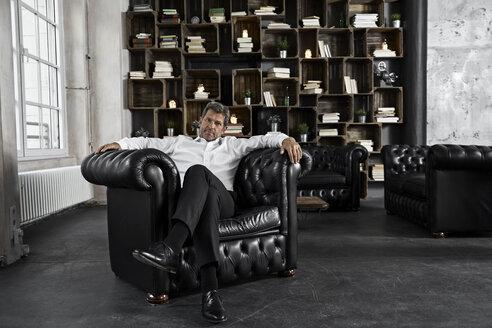 Portrait of mature man sitting in black armchair in loft - PDF01616