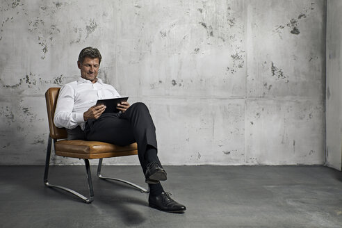 Mature man using digital tablet in front of concrete wall - PDF01619