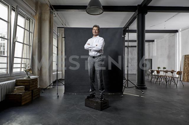 Portrait of mature businessman in front of black backdrop in loft - PDF01625
