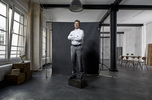 Portrait of mature businessman in front of black backdrop in loft - PDF01625