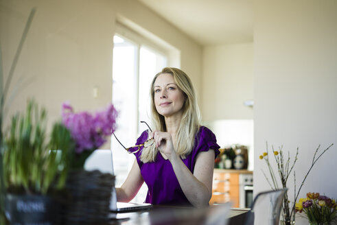 Portrait of businesswoman sitting at table using laptop at home - MOEF01043