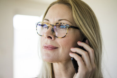 Portrait of blond mature woman wearing glasses on the phone - MOEF01046