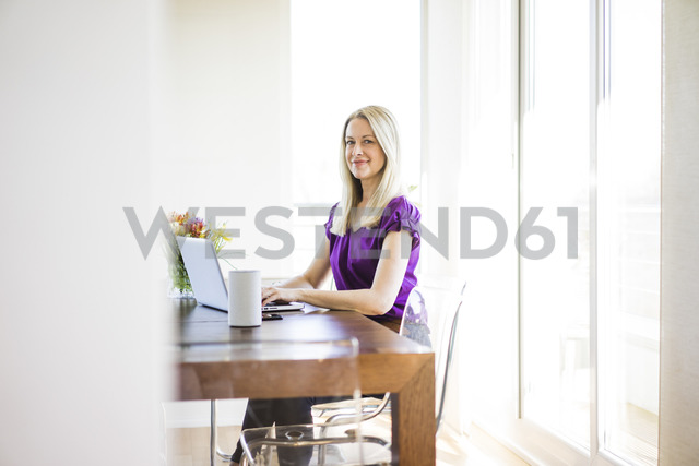 Portrait of smiling businesswoman working on laptop - MOEF01052