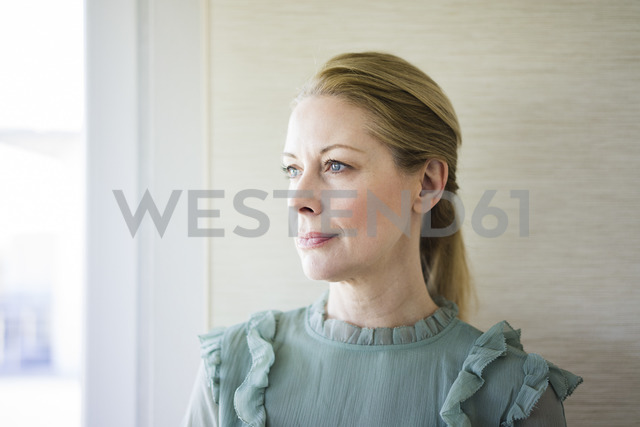 Portrait of blond mature woman looking out of window - MOEF01058