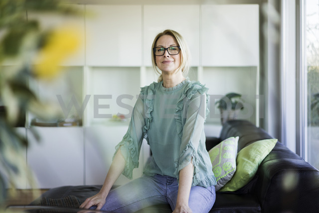 Portrait of content businesswoman sitting on couch - MOEF01061