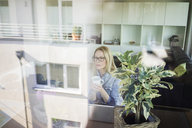Mature businesswoman sitting at  table with cup of coffee looking out of window - MOEF01067