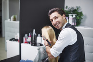 Portrait of smiling hairdresser at work - ABIF00339