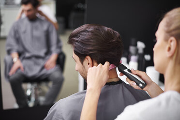 Hairdresser cutting man's hair - ABIF00351