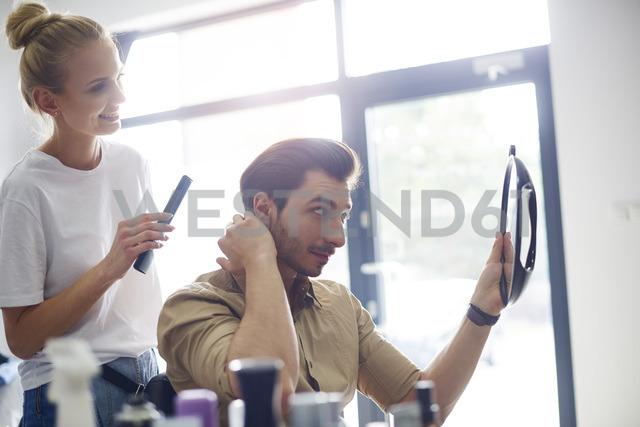 Man checking his haircut at the barber shop - ABIF00354