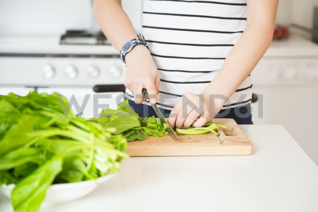 Girl chopping vegetable in the kitchen, partial view - LVF06890