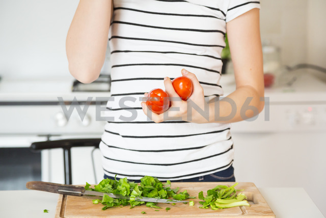 Girl standing in the kitchen holding tomatoes, partial view - LVF06893