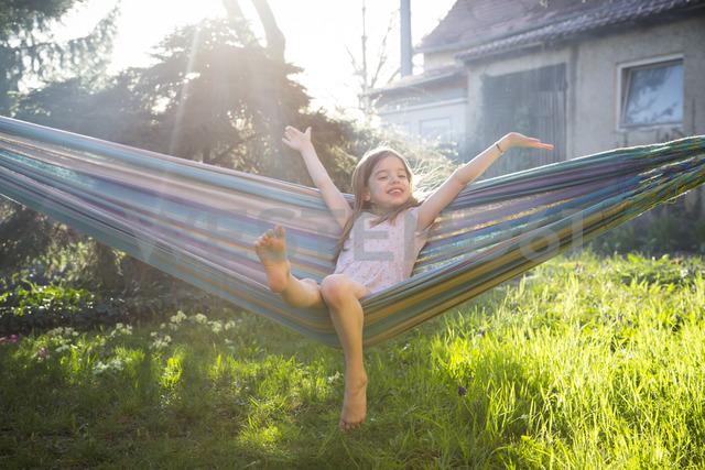 Portrait of happy little girl sitting on hammock in the garden - LVF06904