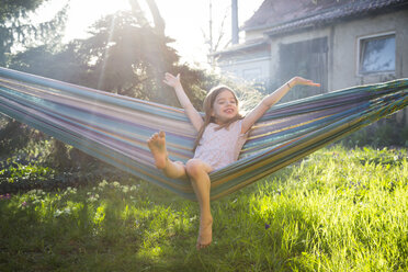 Portrait of happy little girl sitting on hammock in the garden - LVF06904