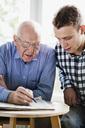 Men solving crossword - MASF07040