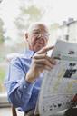 Elderly man reading newspaper - MASF07043