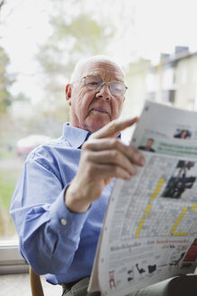Elderly man reading newspaper - MASF07043