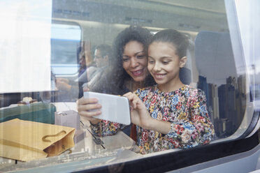 Mother and daughter using camera phone at window of passenger train - CAIF20218