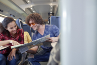 Young couple looking at map on passenger train - CAIF20221