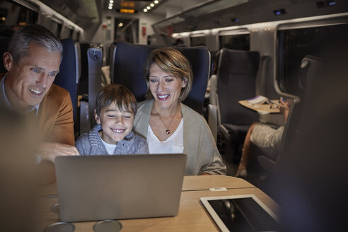 Family using laptop on passenger train at night - CAIF20224