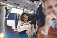 Woman with credit card using contactless payment, paying attendant on passenger train - CAIF20230