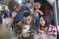 Young friends looking at photos on digital camera on passenger train - CAIF20233