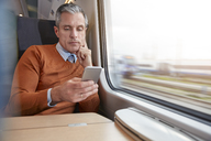 Focused businessman using smart phone at passenger train window - CAIF20239