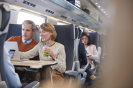Businessman and businesswoman working at laptop, drinking green smoothie on passenger train - CAIF20248