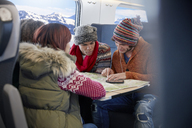 Young friends with map planning on passenger train - CAIF20254