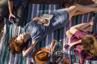 Overhead view young woman with book relaxing on picnic blanket - CAIF20263