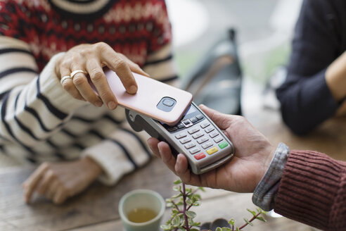 Woman with smart phone using contactless payment - CAIF20278