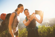 Female rock climbers taking selfie with camera phone - CAIF20281