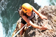 Focused female rock climber hanging from rock above ocean - CAIF20284