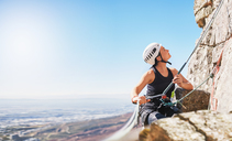 Female rock climber holding rope, looking up - CAIF20287