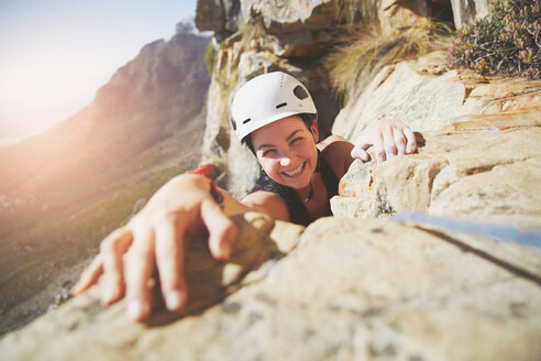 Portrait smiling, confident rock climber reaching for rock - CAIF20290