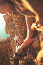 Smiling female rock climber reaching for hand - CAIF20293