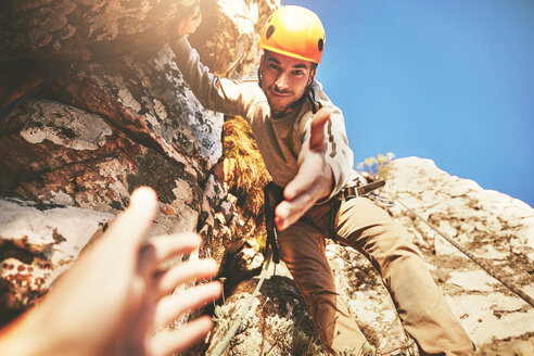 Personal perspective reaching for hand of rock climber - CAIF20296
