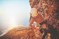 Female rock climber reaching for clip above sunny ocean - CAIF20299