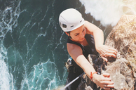Determined, focused female rock climber hanging from rock above sunny ocean - CAIF20305