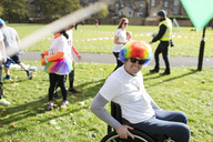 Portrait smiling, playful man in wheelchair wearing clown wig at charity race in sunny park - CAIF20311