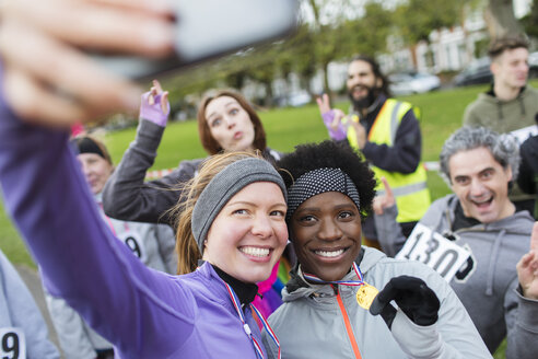 Smiling female runners with medal taking selfie at charity run in park - CAIF20314