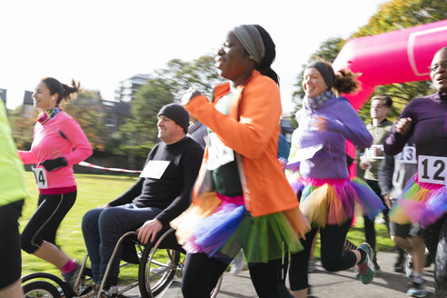 Female runner in tutu running in crowd at charity run in sunny park - CAIF20317