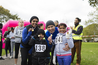 Portrait confident family showing medals at charity run in park - CAIF20320