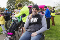 Portrait smiling, confident man in wheelchair showing medal at charity race in park - CAIF20326