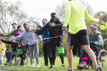 Spectators high-fiving runners at charity run in park - CAIF20332