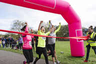 Enthusiastic family runners crossing charity run finish line in park - CAIF20335