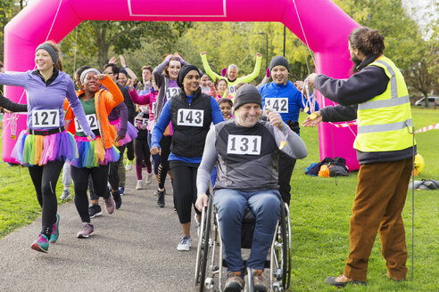 Man in wheelchair and runners receiving medals, crossing charity race finish line - CAIF20338